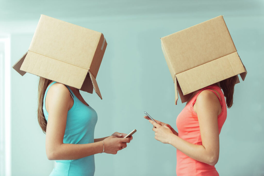 Two Dashers using phones with boxes over their heads illustrating the difficulty of accepting deliveries when Doordash is hiding tips.