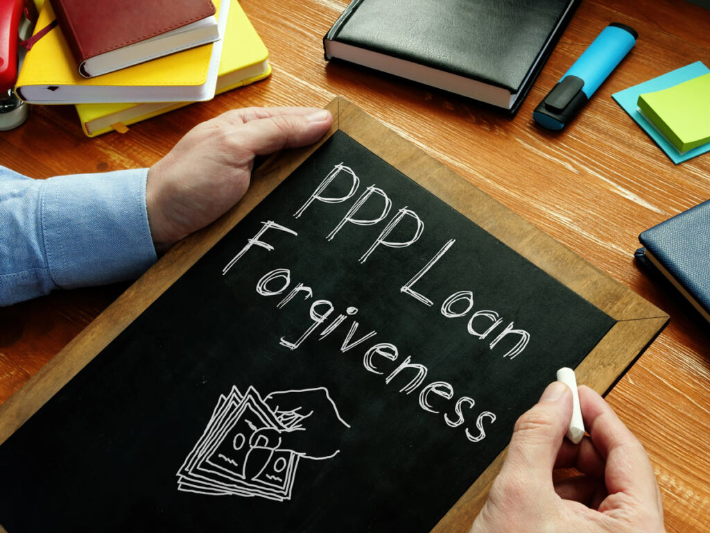 Man writing PPP Loan Forgiveness on a chalkboard on his desk.