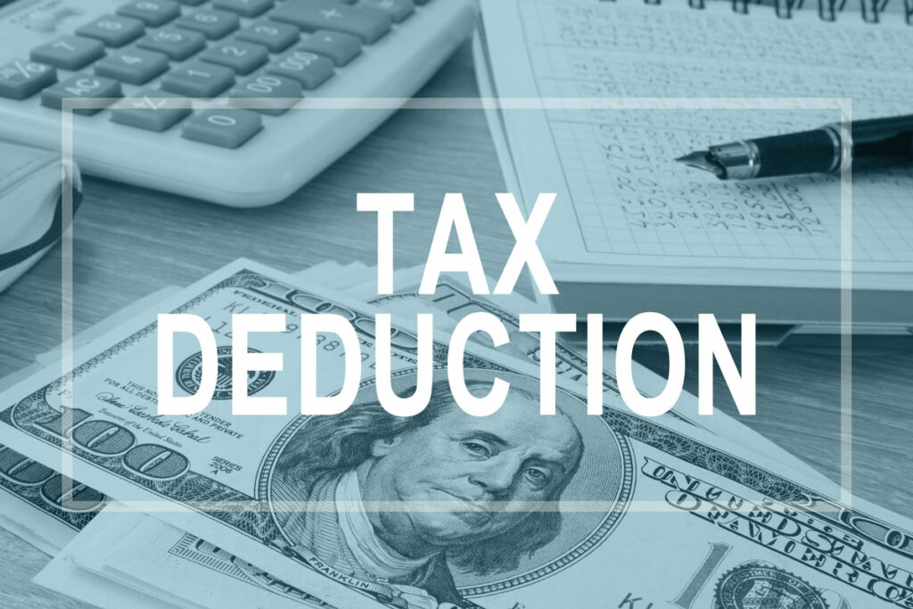 desktop with calculator, itemized list of expenses, and money, with white label over the picture saying Tax Deduction.