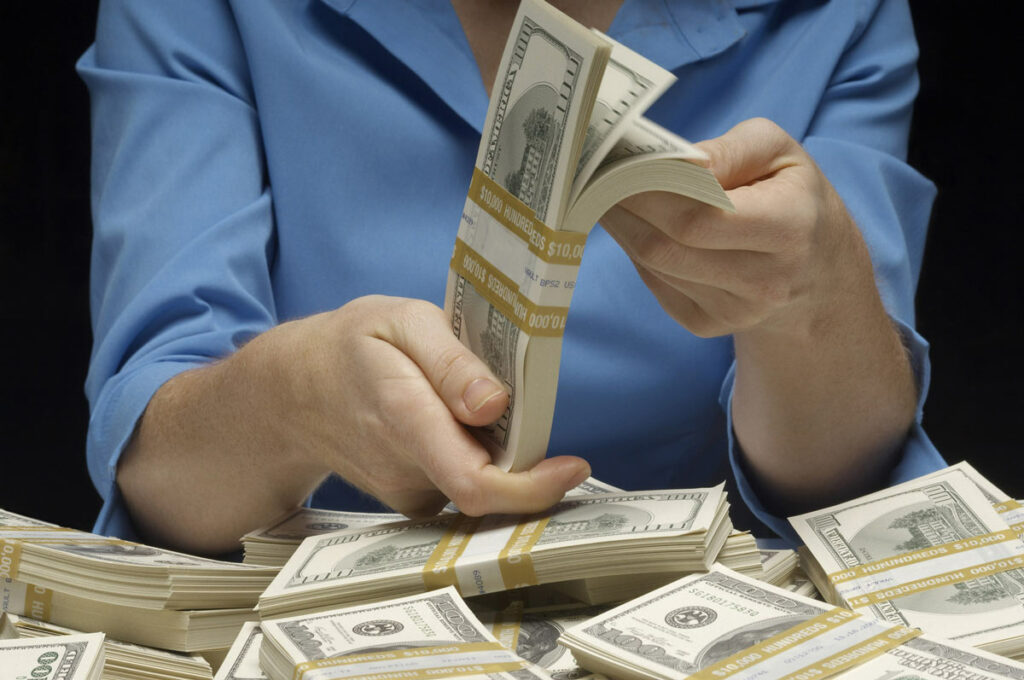 Close up of woman counting her earnings from several sources.