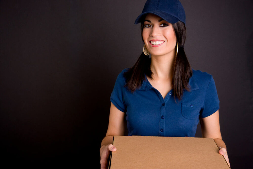 A female delivery driver in a blue uniform holding a couple of pizzas.