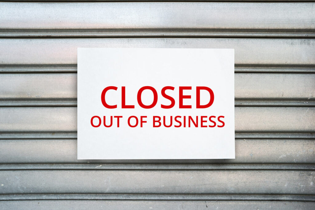 Paper sign on a business billboard that says closed out of business.