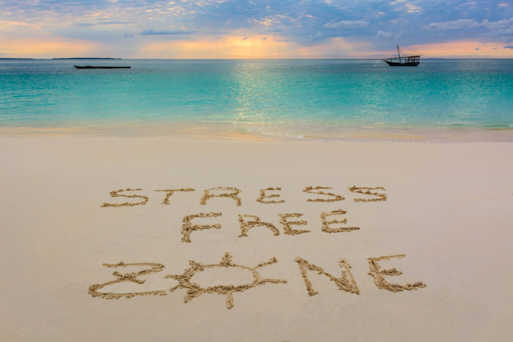 A beautiful ocean sunset with the words Stress Free Zone dug into the sand on the beach.