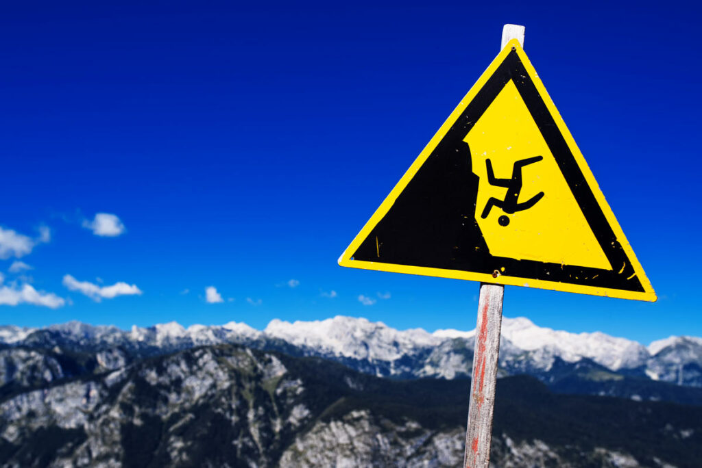 Warning sign off a mountain cliff that shows a figuring tumbling down the cliff.