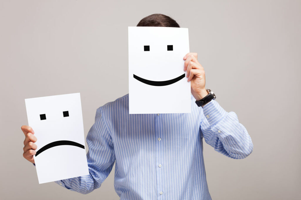 Person holding up a smiley face over his face, and a frown face paper held in the other hand.