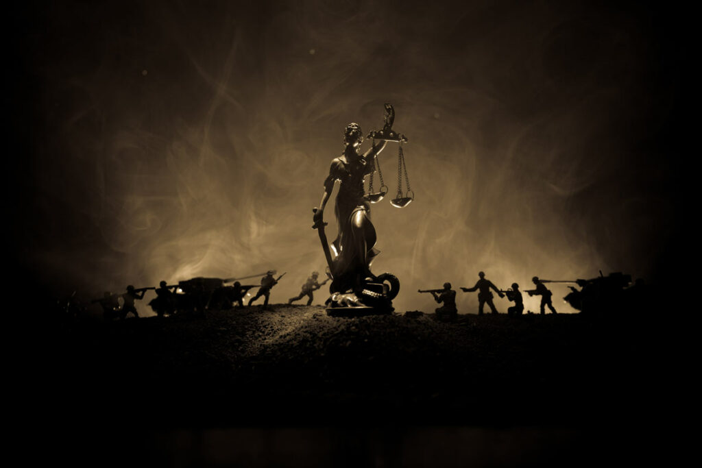 Legal battle concept illustrated by a military battle in the background and with lady justice holding scales of justice in the foreground.