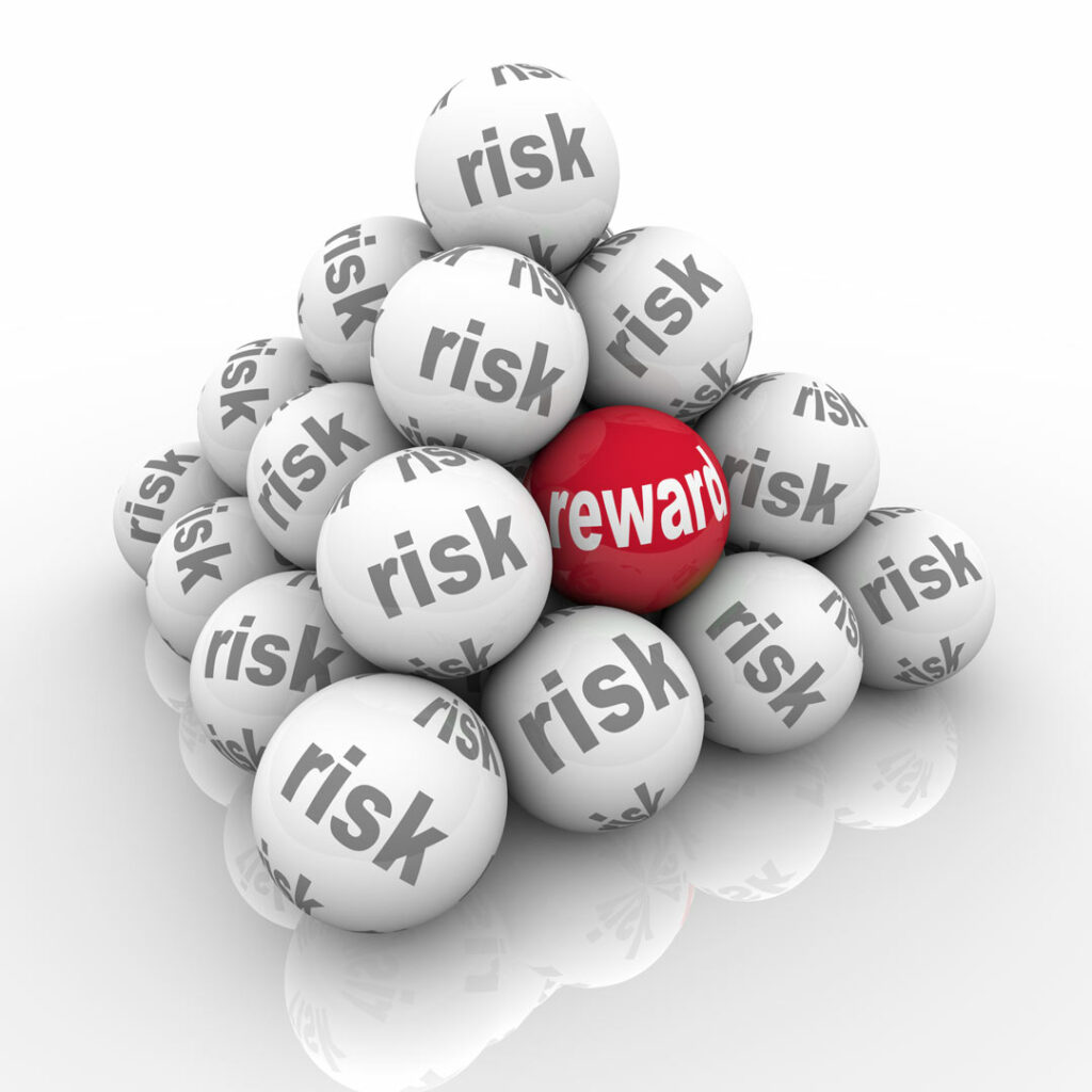 Risk verses reward concept illustrated by a pyramid of balls. All but one of the balls is white with Risk written in grey. One red ball stands out with Reward written in white letters.