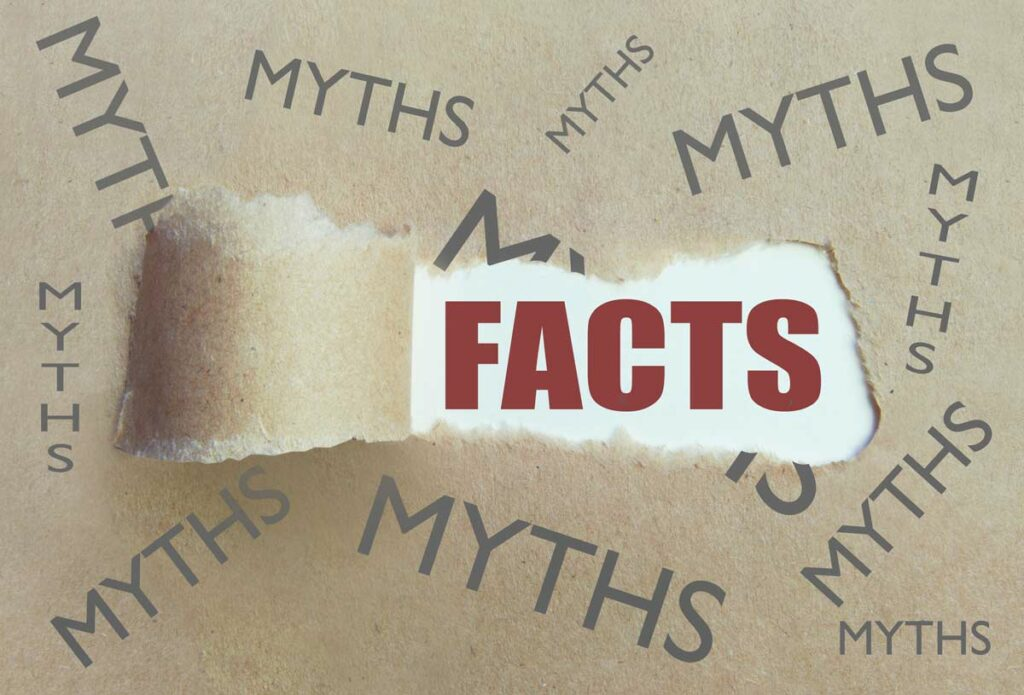 Facts surrounded by myths concept illustrated by brown paper, with the word Myths printed several times and a section torn away to reveal the word Facts.