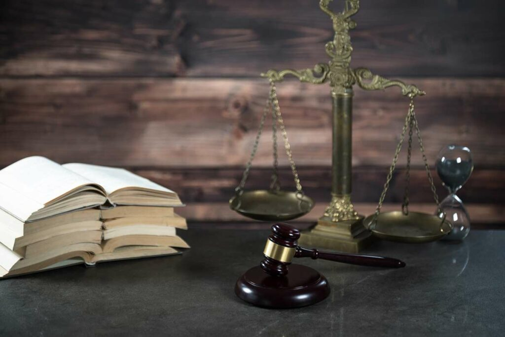 A gavel, law books, hour glass and the scale of justice, symbolizing weighing factors in a legal decision.